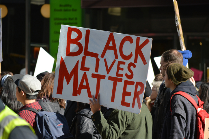 "New York, New York - November 12, 2016: Protester carrying a ""Black Lives Matter"" sign while marching in a ""Trump is not my President"" rally in response to the 2016 Presidential Election of Donald Trump in New York City in 2016."